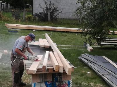 pracownik tnie drewnianą belkę